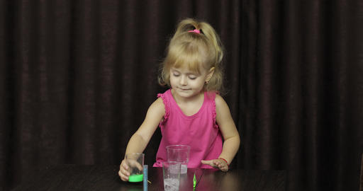 Child having fun making green slime. Mixes ingredients. Kid with hand made toy Live Action
