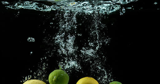 Yellow and Green lemons, citrus limonum, Citrus aurantifolia, Fruits falling into Water against Live Action