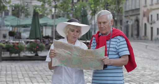 Senior male and female tourists standing with a map in hands looking for route Footage