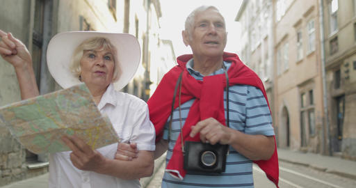 Senior male and female tourists walking with a map in hands looking for route Footage
