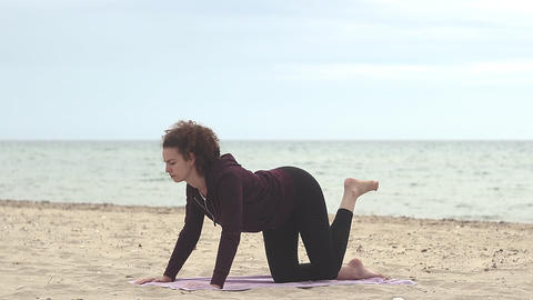 Fitness, sport and healthy lifestyle concept. Young woman doing recreation and exercise on the beach Live Action