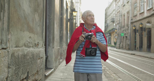 Senior male tourist exploring town and makes a photo with photo camera Live Action
