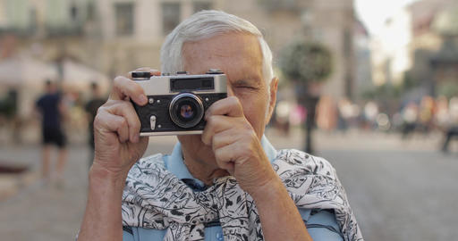 Senior male tourist exploring town and makes a photo with retro photo camera Live Action