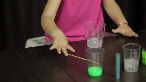 Child hands making green slime. Mixes ingredients. Playing with hand made toy Live Action