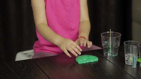 Child hands having fun with green slime. Kid playing with hand made toy slime Footage