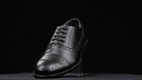 Rotation and approximation of black classic men's shoes on a black background Live Action