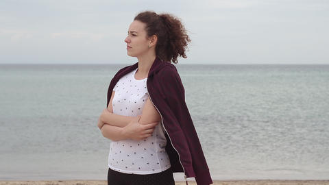 Young woman standing on the beach while wind is blowing. Young woman dress herself with sweatshirt Footage
