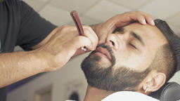 Professional barber using a straight razor shaving his client Live Action