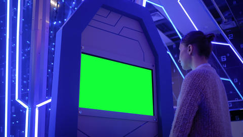 Woman looking at blank green display kiosk at exhibition - green screen concept Footage