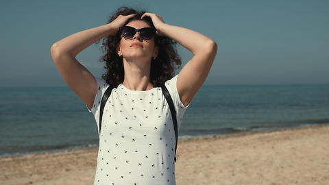 Portrait of beautiful young woman on the beach touching her curly hair Footage