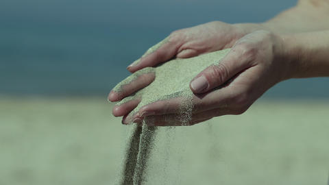 Close up of woman holding dry sand in hand and sand fall between fingers in slow motion Live Action