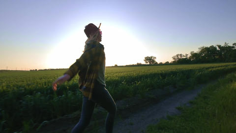 Woman farmer runs along the road along the field. Feels a sense of freedom from Footage