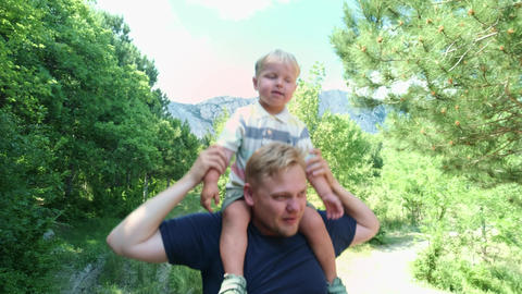 Happy young father holds his son piggyback ride on his shoulders and looking up Live Action