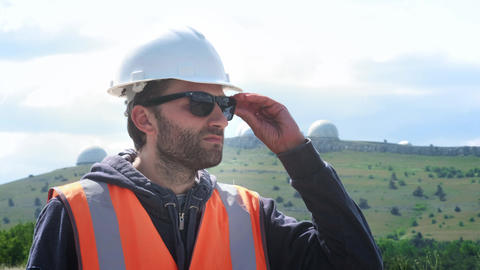 Male engineer or builder in a white helmet and vest wears glasses. Against the Footage