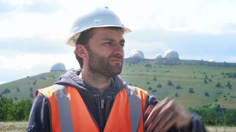 A male engineer or builder in a white helmet and vest, stands against the Footage