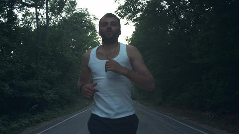 Man running outside in nature at rainy evening. Male runner doing a run at dusk Live Action