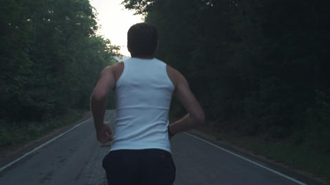Man running outside in nature at rainy evening. Male runner doing a run at dusk Footage
