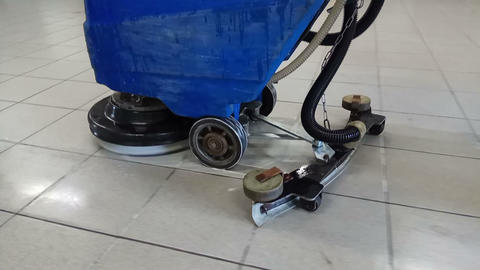 cleaner washes the floor in the building with a washer Footage
