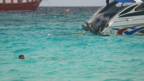 Two men swimming near speedboat Footage