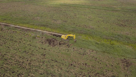 Excavator digging a trench in the field.Aerial video Footage