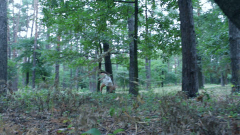 Scared young woman running through forest Footage