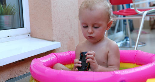 Adorable Baby Playing With Toys In A Mini Pool Live Action