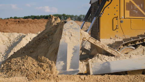 Bulldozer machine moving sand in sand quarry. Mining equipment at quarry Live Action