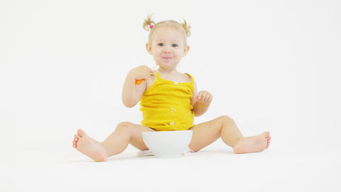Cheerful baby girl eats her meal on white background Live Action
