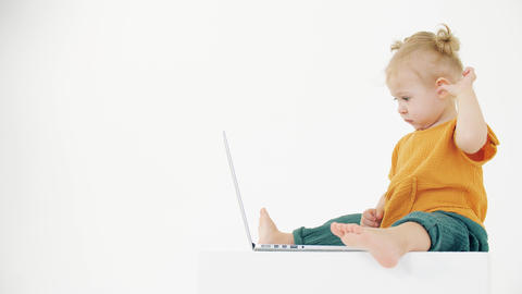 Yawning baby girl looks at the laptop screen on white background. Boring content Live Action