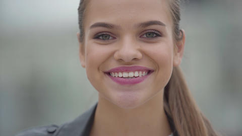 Close-up portrait of carefree confidence happy girl looking at camera outdoors Footage