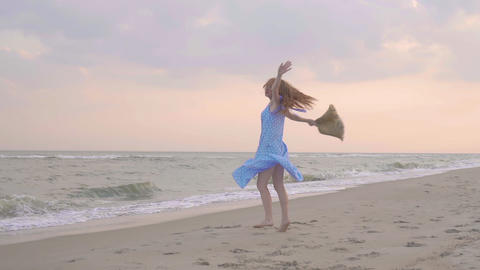 Carefree woman dancing on the sunset on the sea beach. Girl rotate with a straw Footage