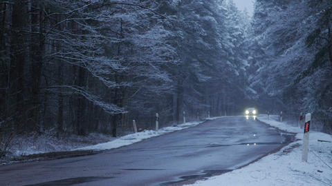 The car moves on a snowy forest road at dusk. Winter season Live Action