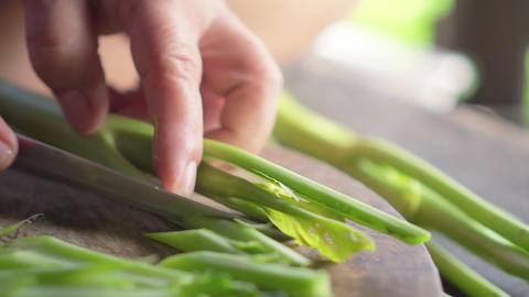Old lady use knife for slicing a chinese kale. Gai lan. vegetarian. Prepare for cooking Footage