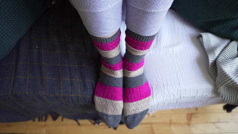 Female legs in brown-pink warm knitted socks close-up on a cozy sofa with a Footage