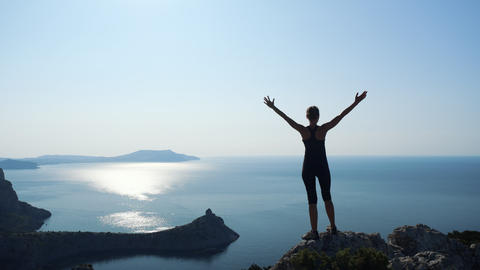 Young inspired woman raises her hands up standing on the top of a mountain above Live Action