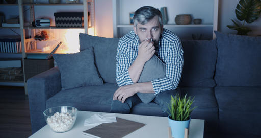 Portrait of sad man watching drama on TV at home wiping eyes with paper tissue Footage