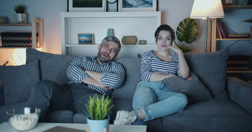 Young family man and woman watching boring movie on TV at home at night yawning Footage