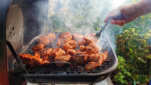 Close up of male hands baking meal outdoors at grill using a fork to turning around meat for not Footage