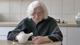 Old lady is pouring alcohol into a glass Live Action