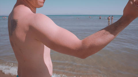 Strong man showing his biceps muscle on sea, beach in summer time. Bodybuilding man has tattoo, Footage