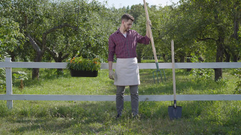 Professional young farmer in garden gloves standing in the green summer garden Live Action