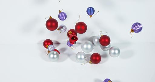 Christmas balls falling on white background, Slow Motion 4K Live Action