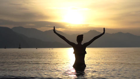 Woman with a heart from her hands above head standing in the sea, slow motion Footage