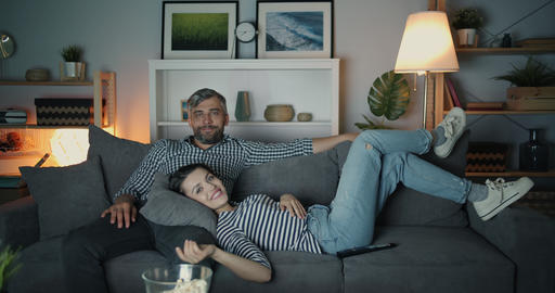 Portrait of girl and guy laughing watching TV at night in cozy apartment Filmmaterial
