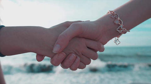 Deal hands, hand shake woman on sand, seaside. Blurry background with empty sea and hand gestures, Live Action