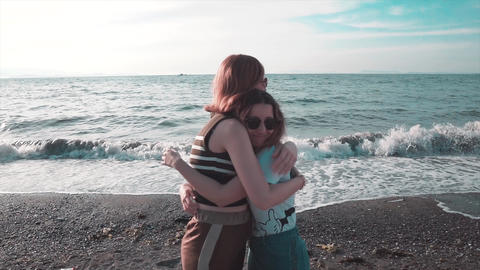 Beautiful best friend girls are hugging on beach near sea, friendship and summer concept Live Action