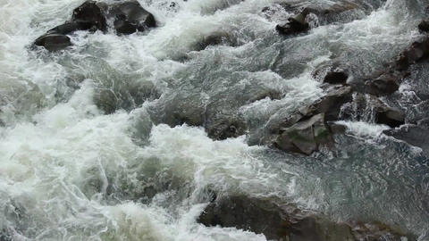 Fast wild mountain river flows on stones Footage