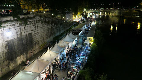 Rome Italy Summer 2016. People by open air summer shops on river Tiber bank Live Action