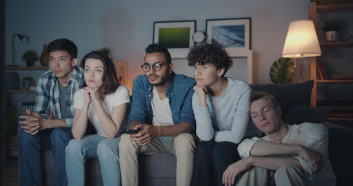 Bored friends choosing TV program clicking remote control at home at night Filmmaterial
