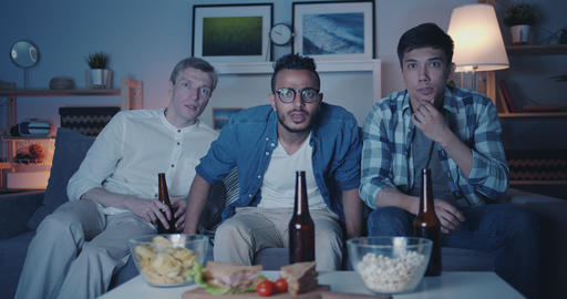 Portrait of handsome guys friends watching TV at night with scared faces Filmmaterial
